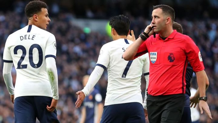 Dele Alli looks at referee Christopher Kavanagh as VAR confuses matters following the midfielder's goal
